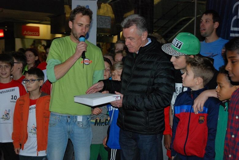 Projektleiter Pascal Pauli übergibt zusammen mit den Spielern vom Swiss Cup das Buch an Ex-Nati-Trainer Ottmar Hitzfeld.
